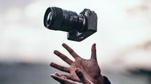 Превью обои фотоаппарат, руки, подбрасывать, левитация, камера