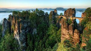 Превью обои мост, скалы, высота, лес, хвойный, облака, гармония