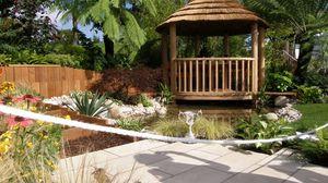 Превью обои беседка, сад, плитка, кубок, тень, растительность, цветы, пальмы, озеро, дорожка