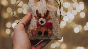 Превью обои подарок, новый год, рождество, олень, рука