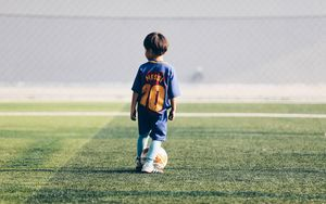 Превью обои ребенок, футболист, футбол, футболе поле, мяч, газон