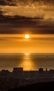 Превью обои солнце, закат, побережье, море, город, темный