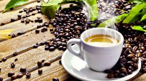 Превью обои стол, зёрна, листья, блюдце, чашка, кофе, пенка, дымок, напиток