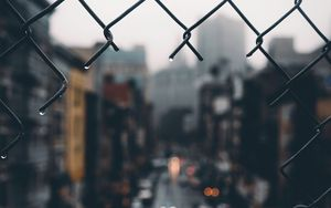 Превью обои забор, сетка, дыра, дождь, город, размытость